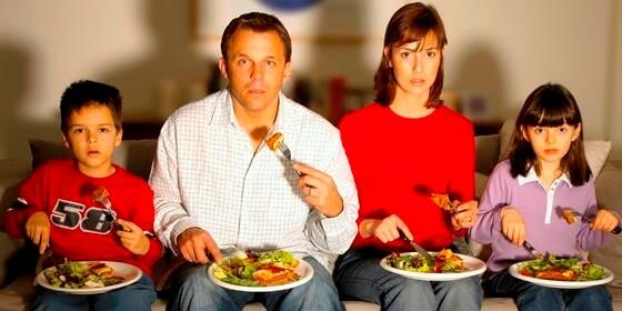 Семья с едой перед ТВ